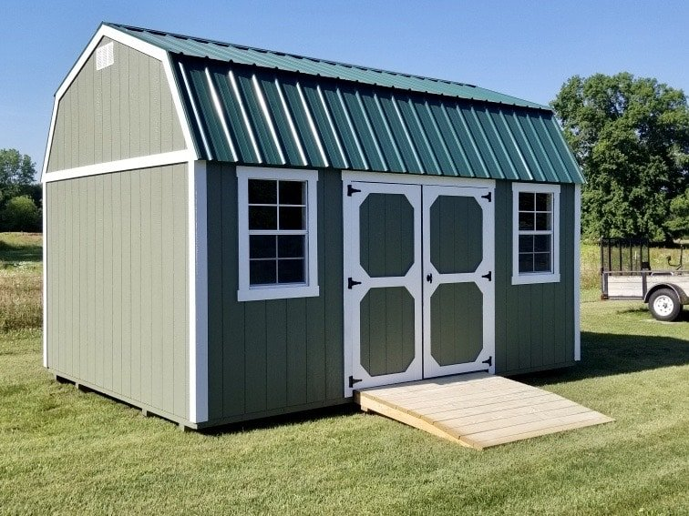 Dark Gray Amish Lofted Garden Shed next to trailer with a heavy duty ramp