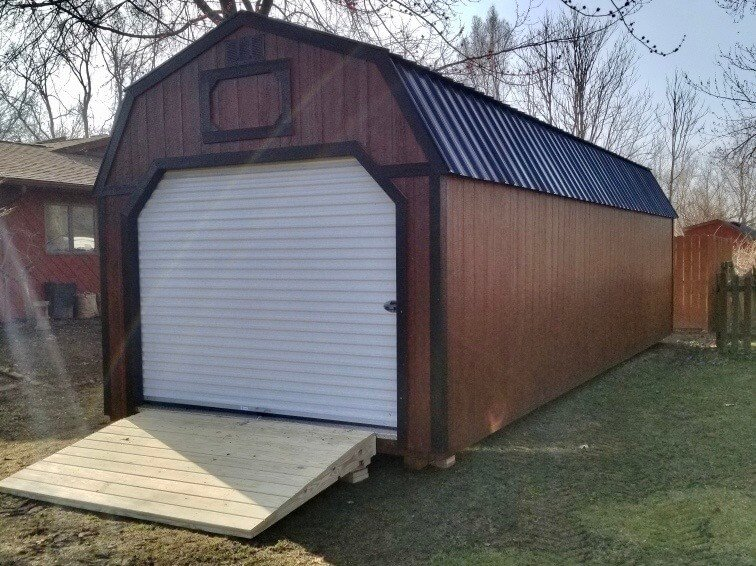 Lofted Amish Garage with ramp in backyard of a customer